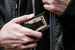 man putting wallet in pocket