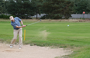 Golfer uding a wedge in the sand