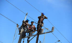 lineman wearing proper footwear on a pole