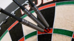 dartboard with steel tip darts thrown in